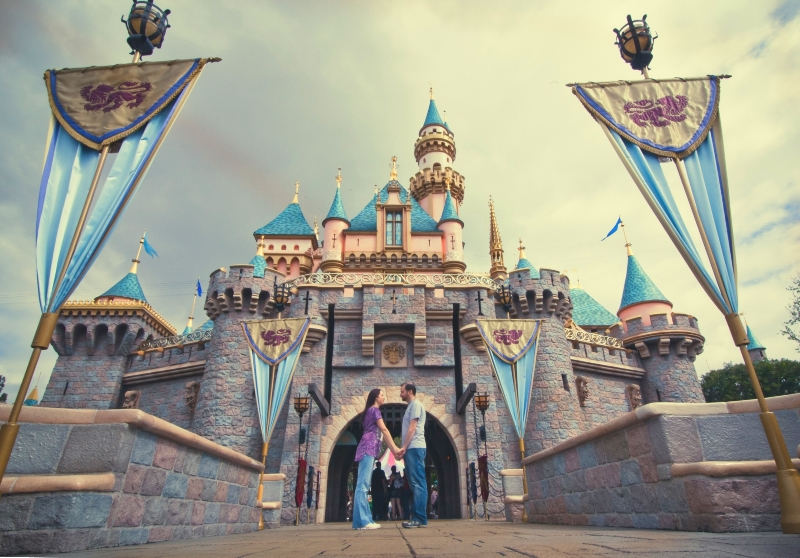 Couple posing in front of Sleeping Beauty Castle at Disneyland