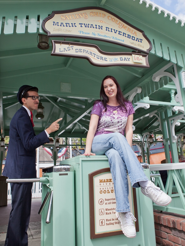 Girl sitting on turnstile while cast member points at her