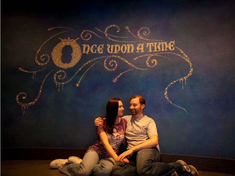 "Couple sitting below mural that reads ""once upon a time"""