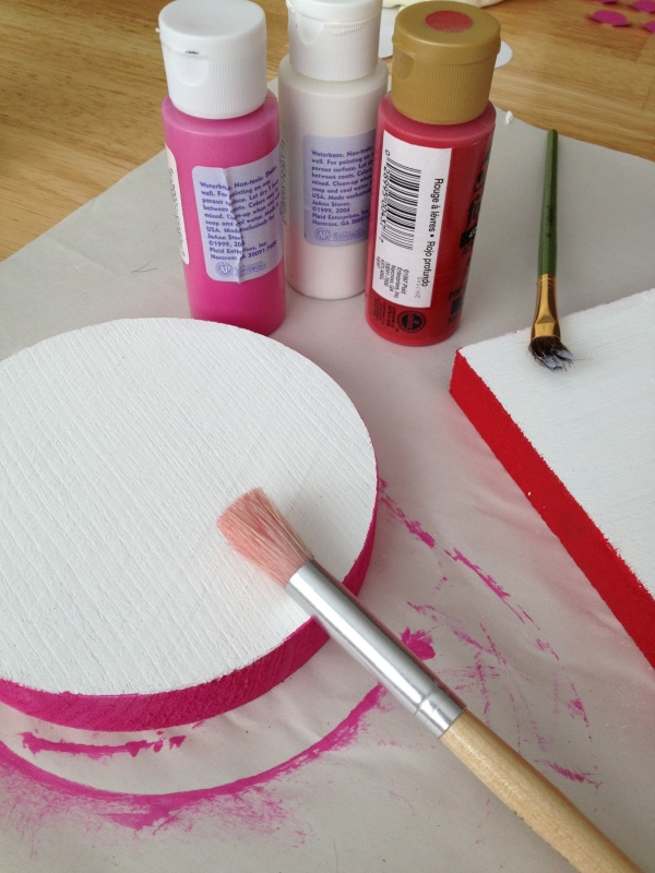 Art supplies, wood block and pink and red paint bottles