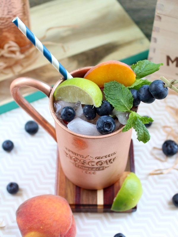 Copper mug containing Moscow Mule alcoholic drink, garnished with mint leaves, lime slices, peach slices, and blueberries