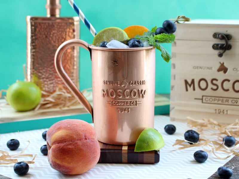 Copper mug containing Moscow Mule alcoholic drink, garnished with mint leaves, lime slices, peach slices, and blueberries. A wooden box and copper flask are in the background.