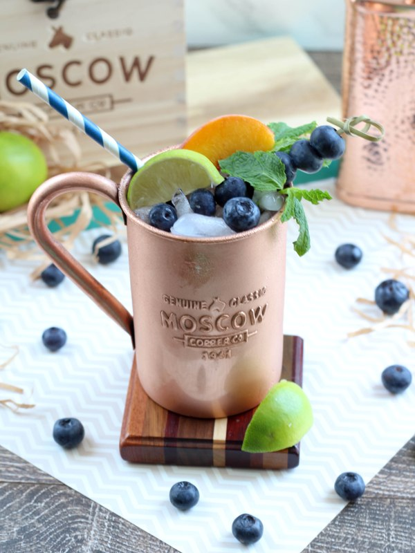 Cpper mug containing Moscow Mule alcoholic drink, garnished with mint leaves, lime slices, peach slices, and blueberries