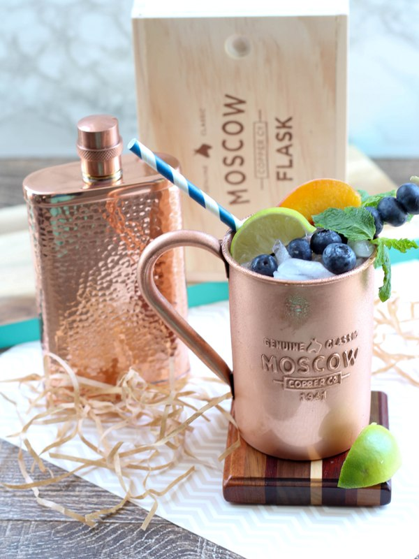 Copper mug containing Moscow Mule alcoholic drink, garnished with mint leaves, lime slices, peach slices, and blueberries. Next to mug is a hammered copper flask.