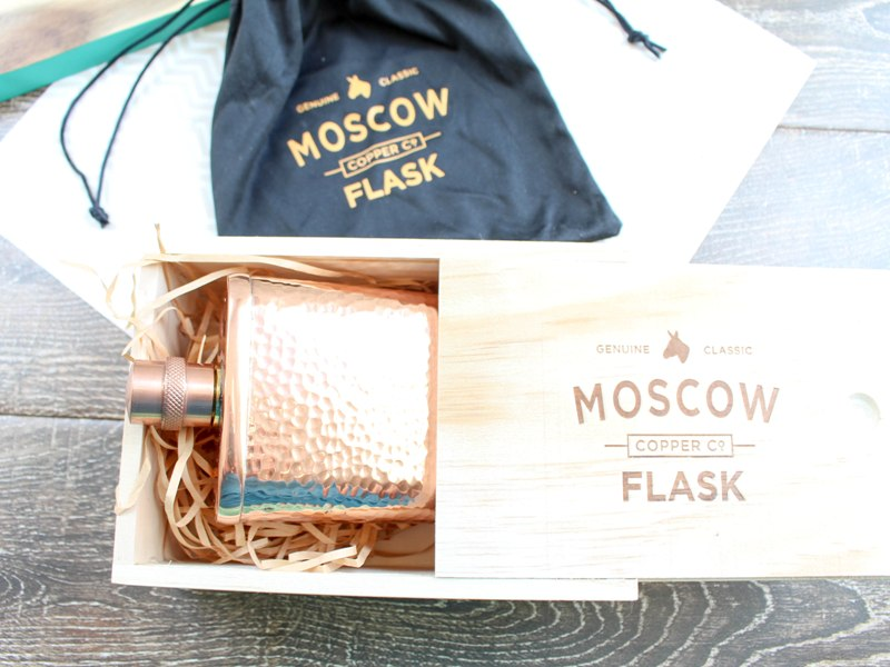 "Wooden box containing hammered copper wooden flask, laying on top of a black velvet gift bag with ""Moscow Flask"" logo."