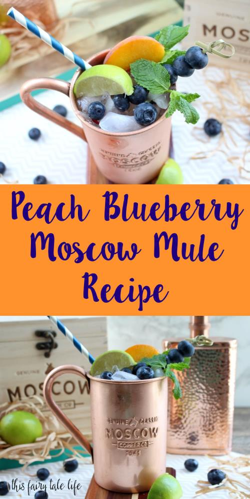 "Copper mug containing Moscow Mule alcoholic drink, garnished with mint leaves, lime slices, peach slices, and blueberries, with text overlay that reads, ""Peach Blueberry Moscow Mule Recipe."""