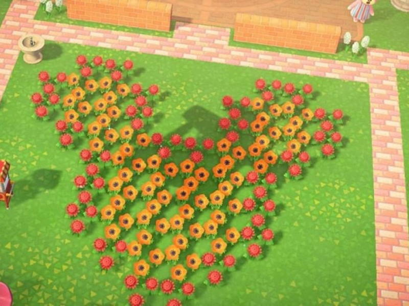 Screenshot from Animal Crossing: New Horizons video game showing red and orange flowers arranged in the shape of Mickey Mouse head