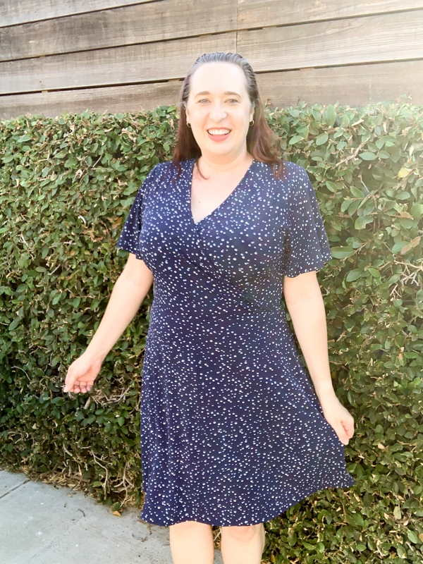 Woman wearing blue polka dot dress and twirling