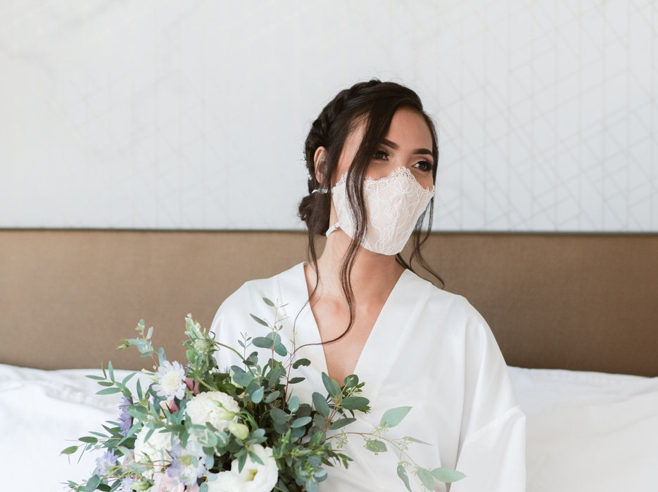 Woman with dark hair wearing white face mask and white robe holding bouquet of white flowers