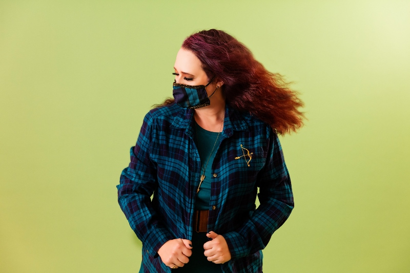 Woman dressed in clothing inspired by Merida from the Disney/Pixar movie Brave, plus wearing a matching cloth face mask