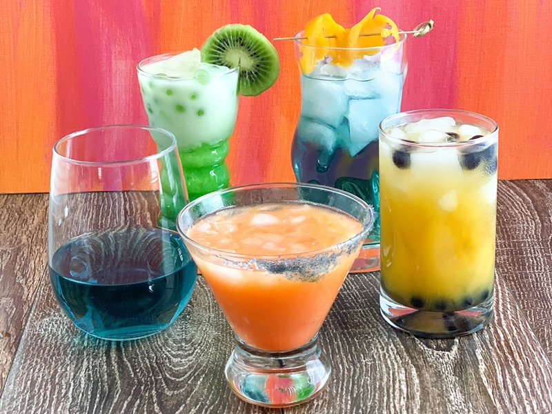 Five different colorful cocktails in different shaped glasses