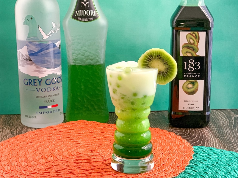 Green cocktail with kiwi fruit garnish