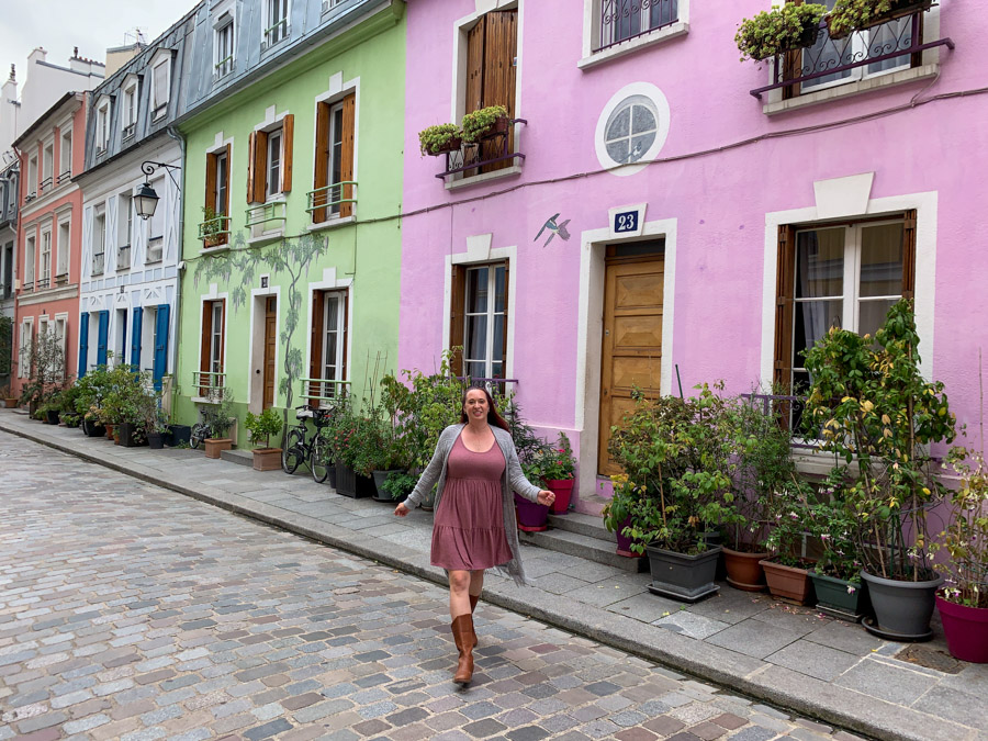 Woman walking on street in front of colorful row houses