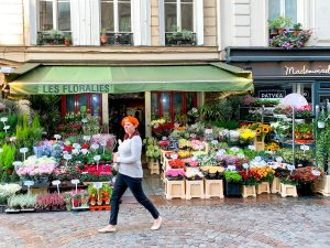 Woman walking in front of flower shop in Paris France