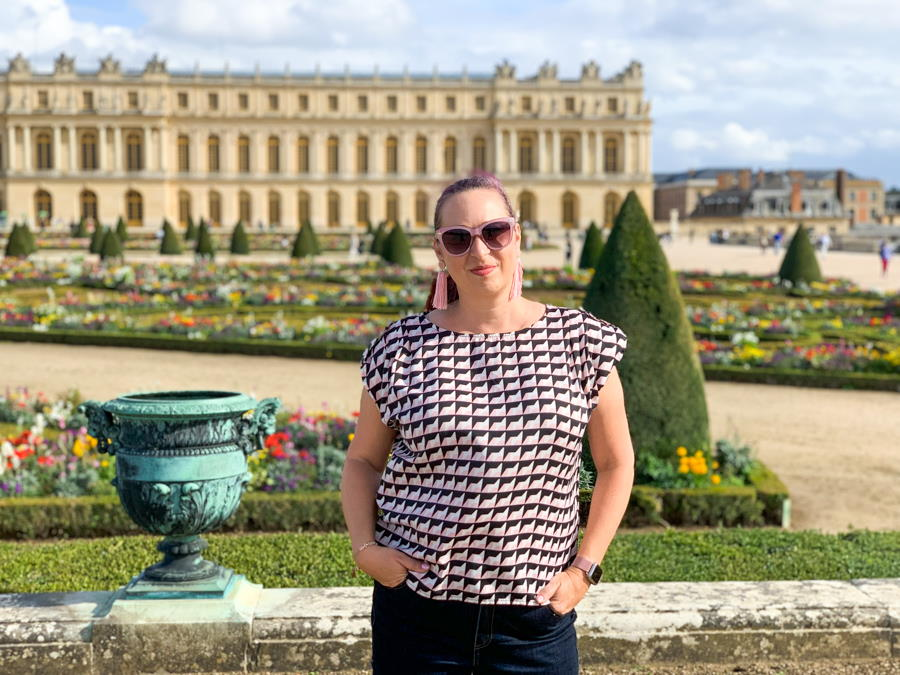 Woman standing in front of Versailles palace in France