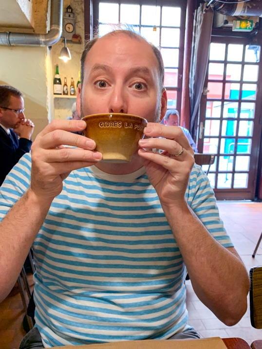 Man drinking cider from bowl