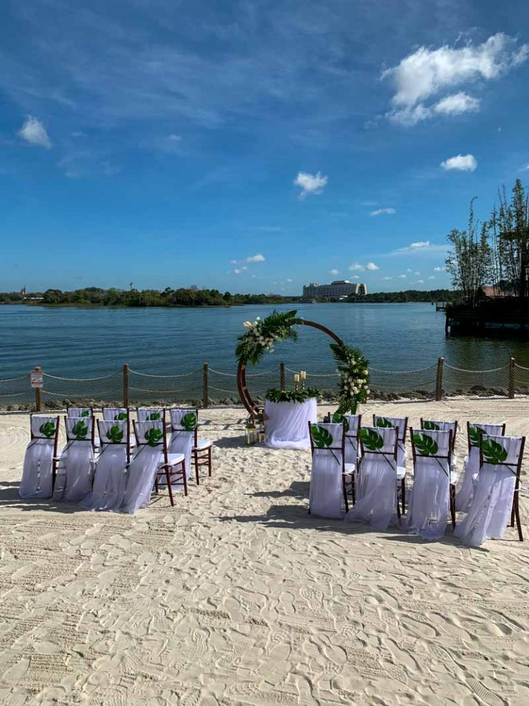 Wedding ceremony set up with white chairs at luau beach at disney's polynesian resort