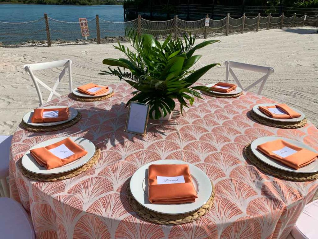 Wedding reception table with orange lace tablecloth and orange folded napkins