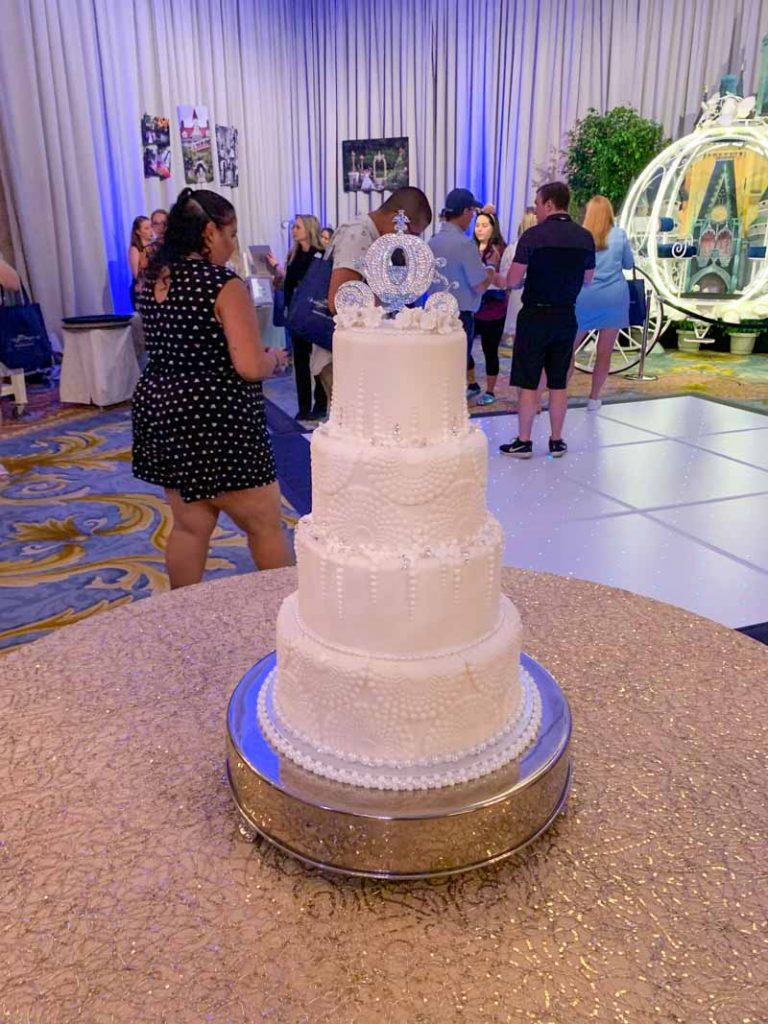 White 4 tiered wedding cake with Cinderella carriage cake topper