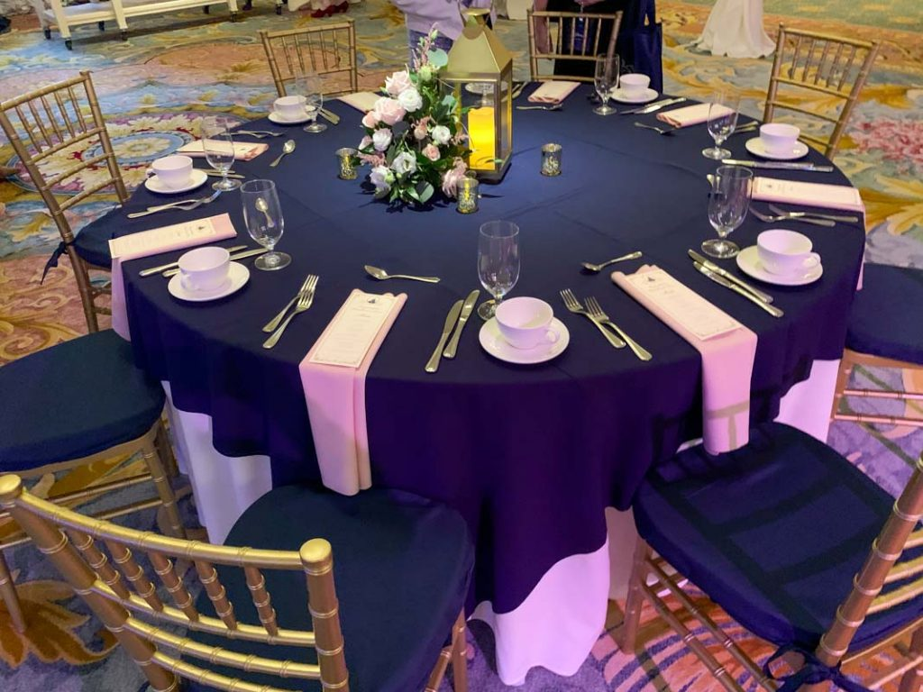 Wedding reception table with navy blue tablecloth and white napkins