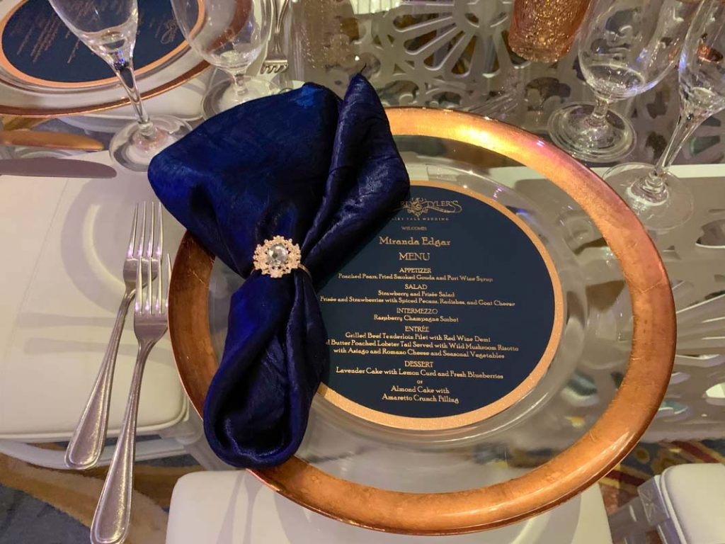 Close up of reception table with gold charger and navy blue folded napkin