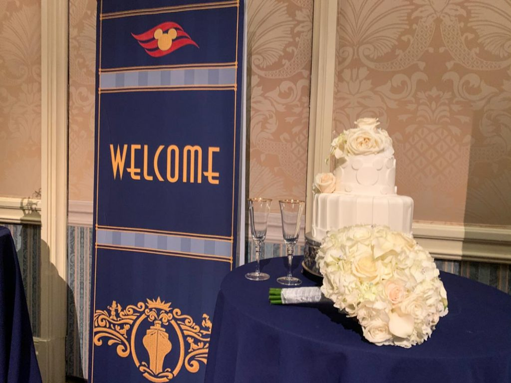 "Disney Cruise Line sign that reads ""welcome"" next to white two tier wedding cake"