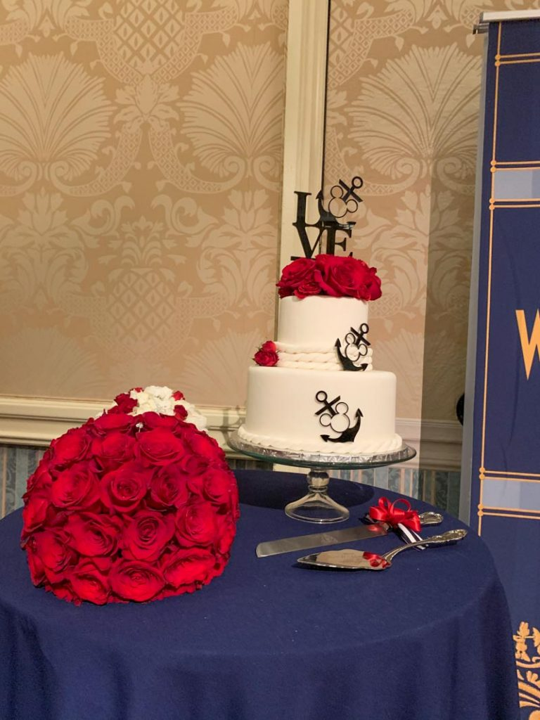 two tier cake with red roses on top, and red roses bouquet