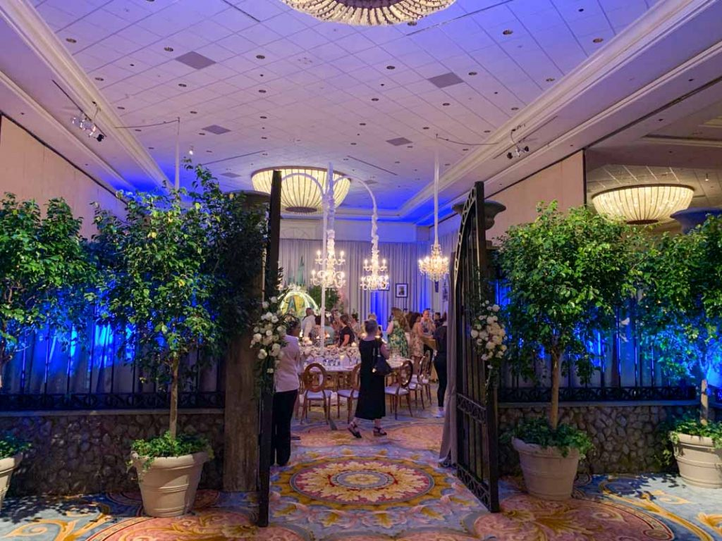 wedding reception ballroom entrance with faux trees and iron gates