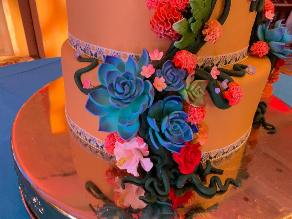 Close up of blue and pink roses made of icing on a wedding cake