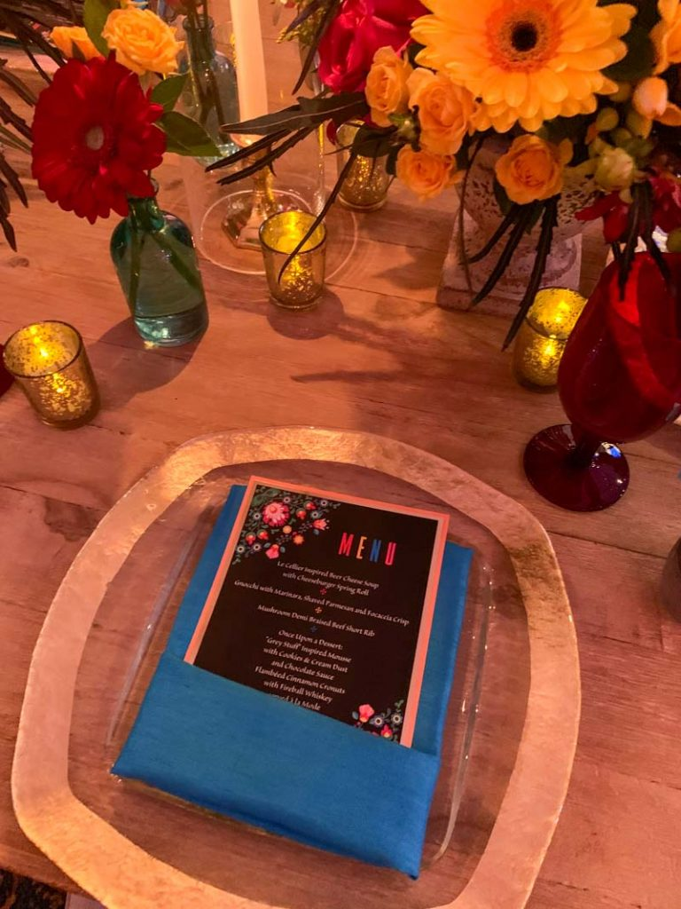 Close up of colorful wedding reception menu and blue folded napkin
