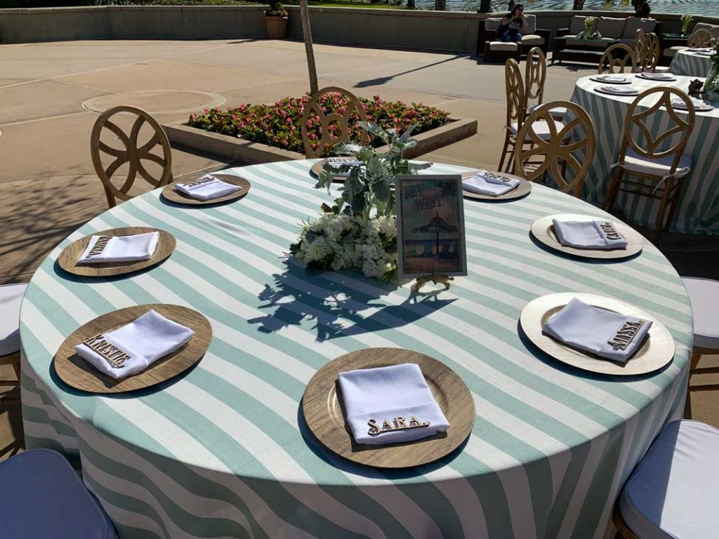 close up of wedding reception table with green striped tablecloth
