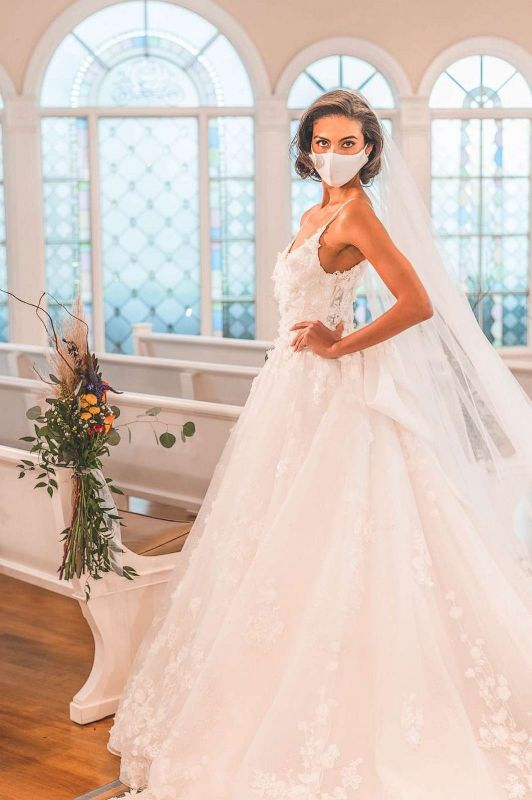 Woman wearing wedding gown and white face mask