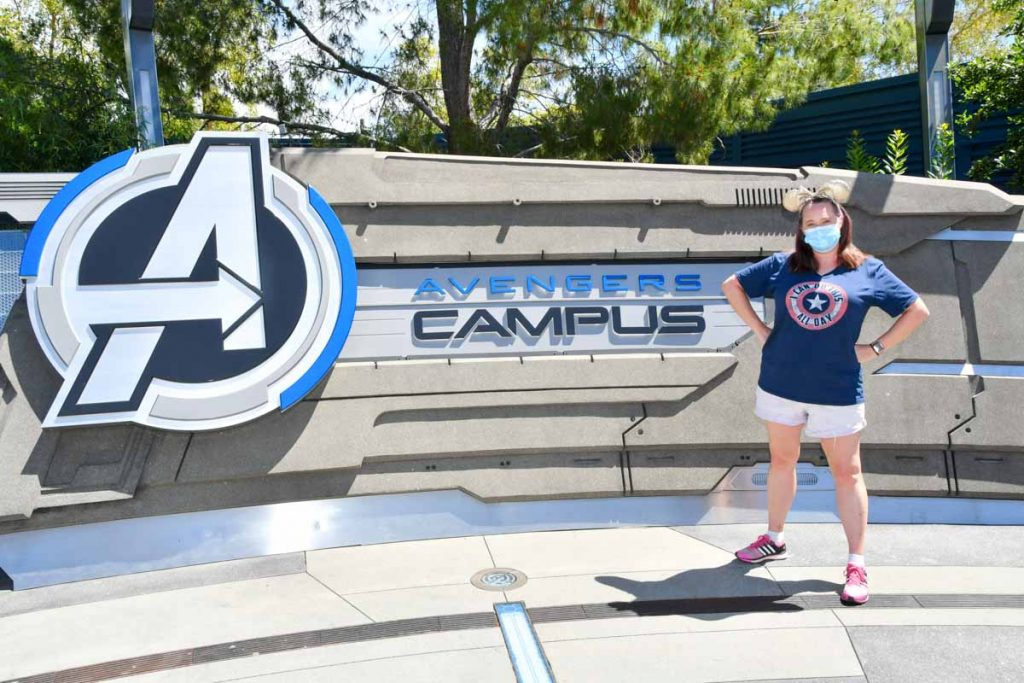 """Woman standing in front of sign that reads """"Avengers Campus"""""""