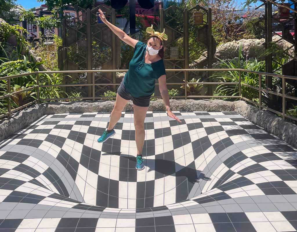 Woman posing with optical illusion floor at Avengers Campus