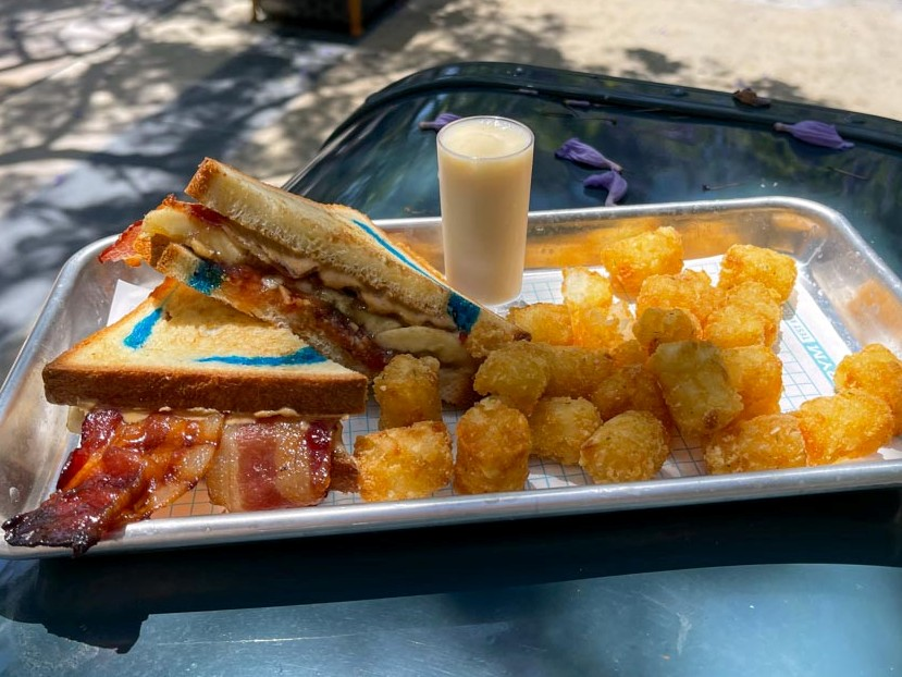 Sandwich with blue swirls in the bread and bacon hanging out next to side of crispy potato bites