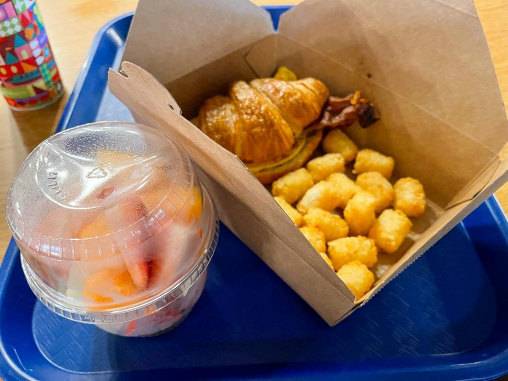 Blue tray with breakfast sandwich, tater tots, and cup of fruit