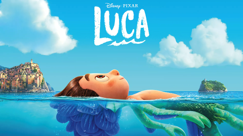 Luca laying in water. Above the water he is human form. Below the water's surface he is a sea monster.