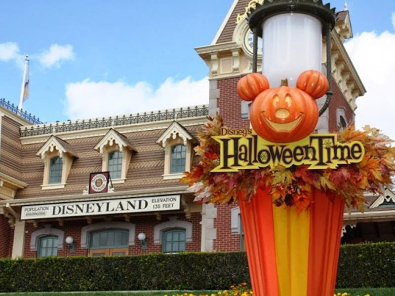 """Close up of Mickey Mouse shaped pumpkin sign that reads """"Halloweentime"""" with Disneyland Railroad station in the background"""