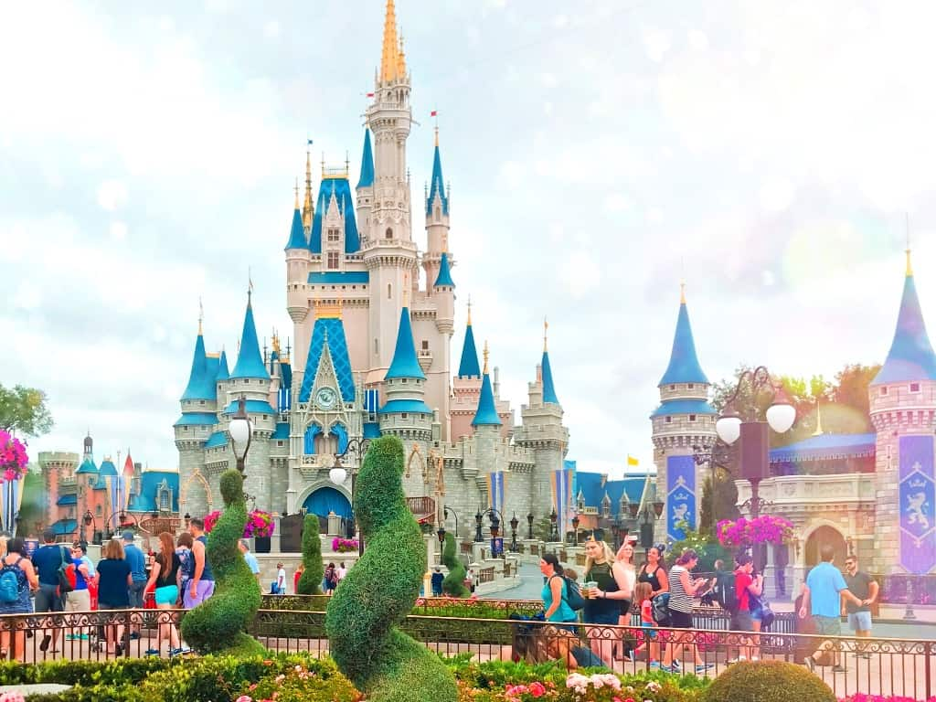 Cinderella Castle at Magic Kingdom at Walt Disney World in Orlando Florida. The castle is a pale pink with light blue roofing and turrets.