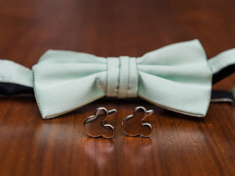 Mint green bowtie next to 2 cufflinks shaped like Mickey Mouse
