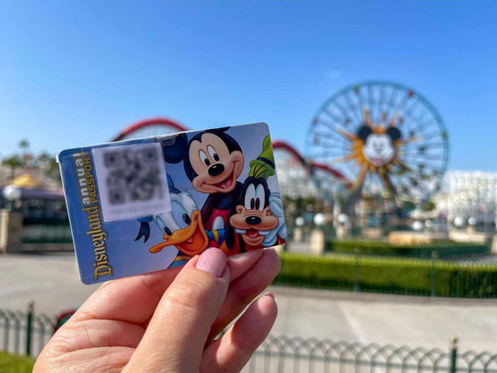 Hand holding up a Disneyland Annual Pass card with photopass code taped to it