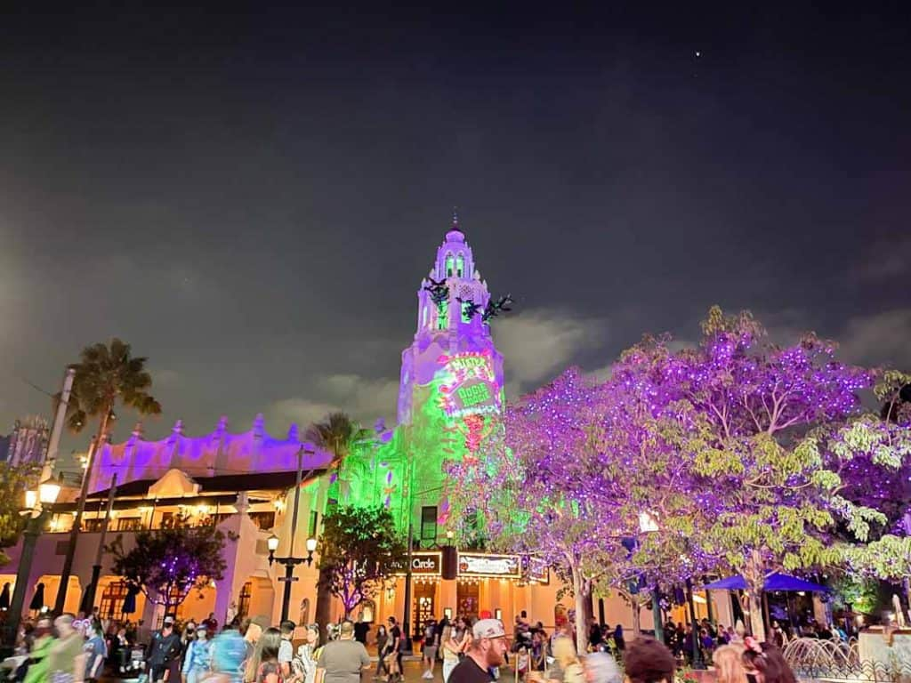 Carthay Circle Restaurant bell tower lit up in green and purple during Oogie Boogie Bash