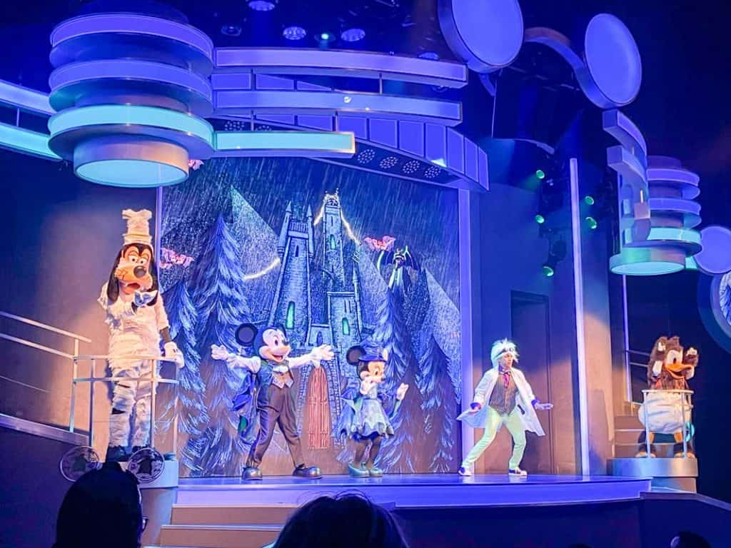 Goofy, Mickey Mouse, Minnie Mouse, and Donald characters on stage at Disneyland. They are dressed in Halloween costumes.